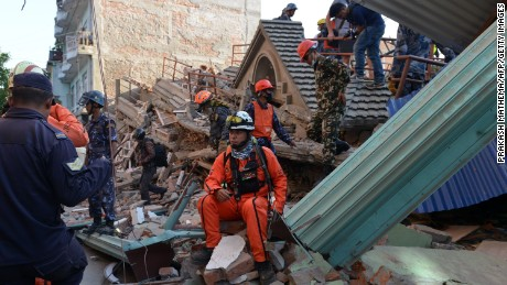 Rescue team officials including one from Mexico (C) look on during their search for survivors at a collapsed building in Kathmandu May 12, 2015, after an earthquake struck.