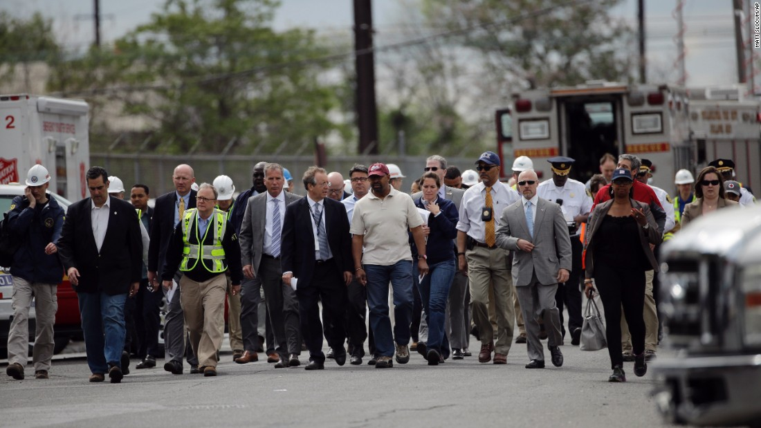 Philadelphia Mayor Michael Nutter, at center in the maroon hat, walks with other officials to a news conference near the crash site on May 13.