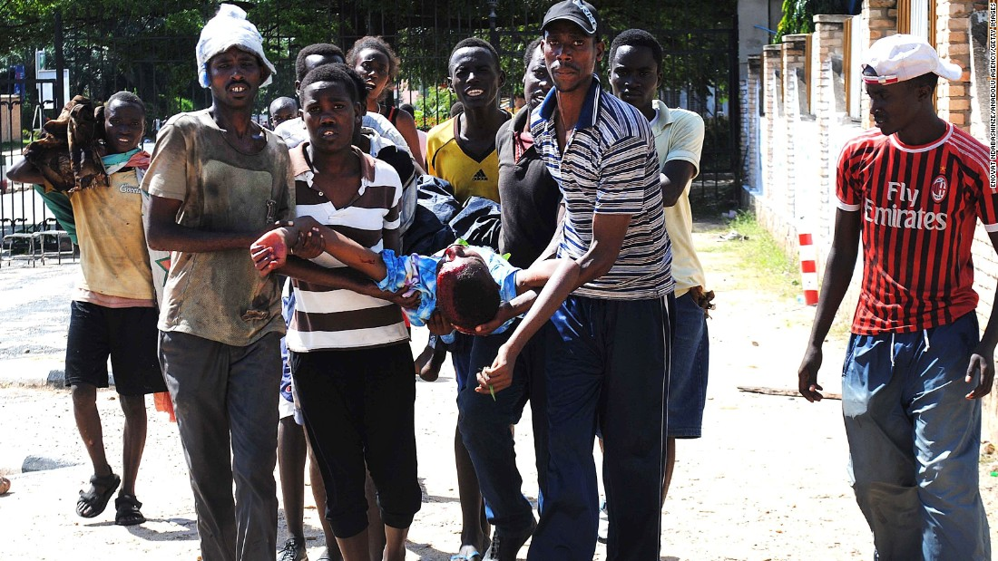 Burundians carry an injured man after security forces clashed with demonstrators in Bujumbura on May 13.
