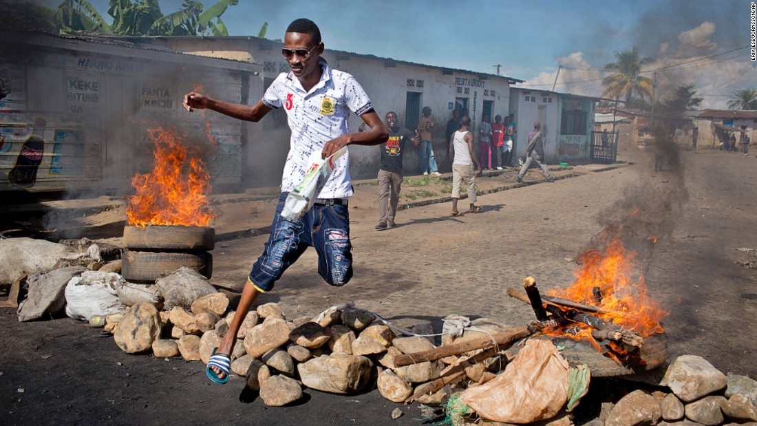 A civilian jumps over a barricade erected by residents to protect themselves from police in Bujumbura on Thursday, May 14.