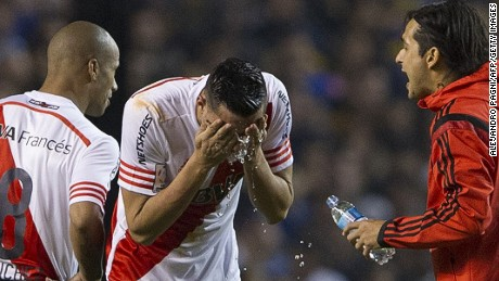 Argentina's River Plate defender Ramiro Funes Mori (C) pours water on his face after getting reached by tear gas before the start of the second half of their Copa Libertadores 2015 round before the quarterfinals second leg football match against Boca Juniors at La Bombonera stadium in Buenos Aires, Argentina, on May 14, 2015.