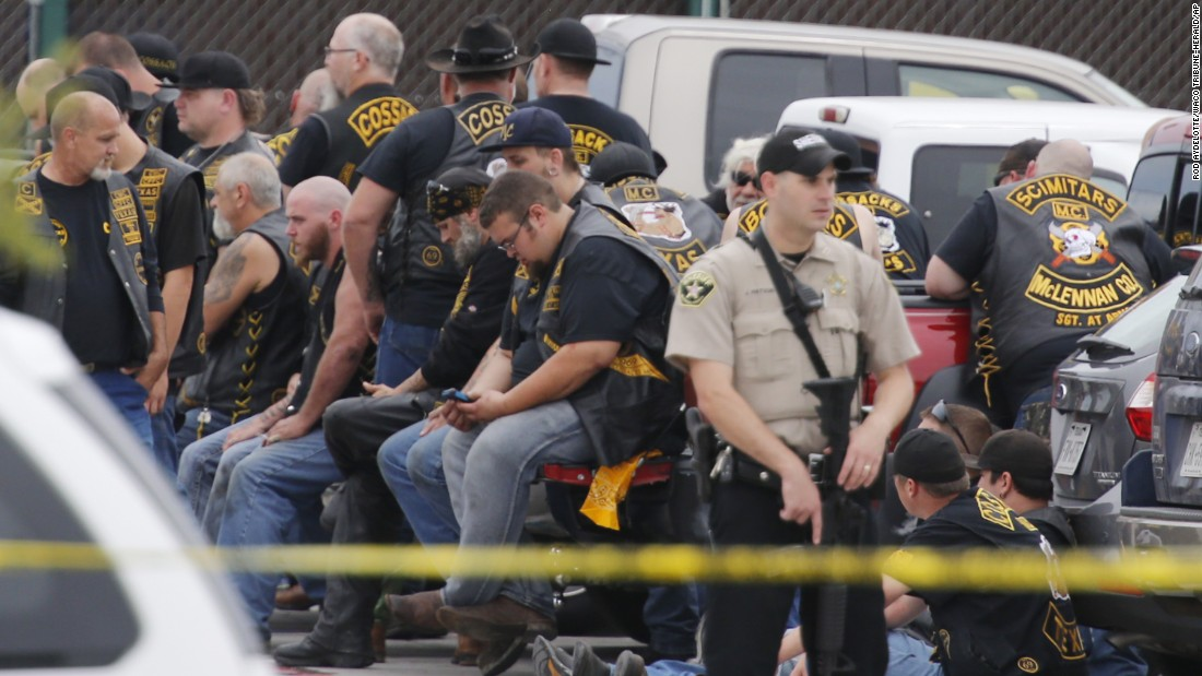 A McLennan County deputy stands guard near a group of bikers.
