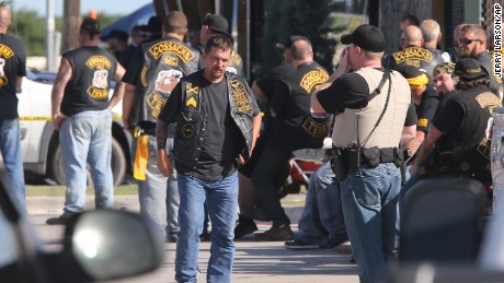 People stand as officers investigate a shooting in the parking lot of the Twin Peaks restaurant Sunday, May 17, 2015, in Waco, Texas. Authorities say that the shootout victims were members of rival biker gangs that had gathered for a meeting. (AP Photo/Jerry Larson)
