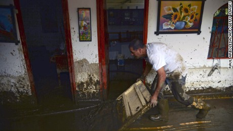 A man cleans his house after a landslide in Salgar municipality, Antioquia department, Colombia.