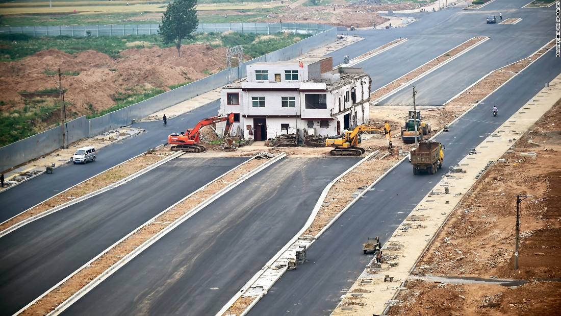 "A three-story house stands in the middle of a newly built road in China's Henan province on May 16, 2015. Construction was put to a halt as the owner refused to move because of a dispute about compensation. Like a nail that refuses to be hammered down, the dwelling is one of many ""nail houses"" that have sprung up in China as some homeowners resist development of their land or hold out for more money. According to construction workers, the owner is still living inside the house even though the rest of the road is complete."