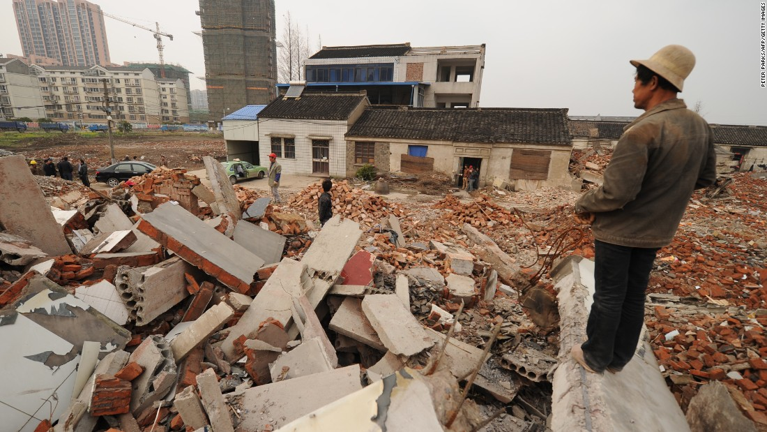 This picture taken on March 13, 2013 shows a worker looking out over a rubble-filled construction site where 75-year-old Yao Baohua's house still stands in Changzhou, a city in eastern China's Jiangsu province.