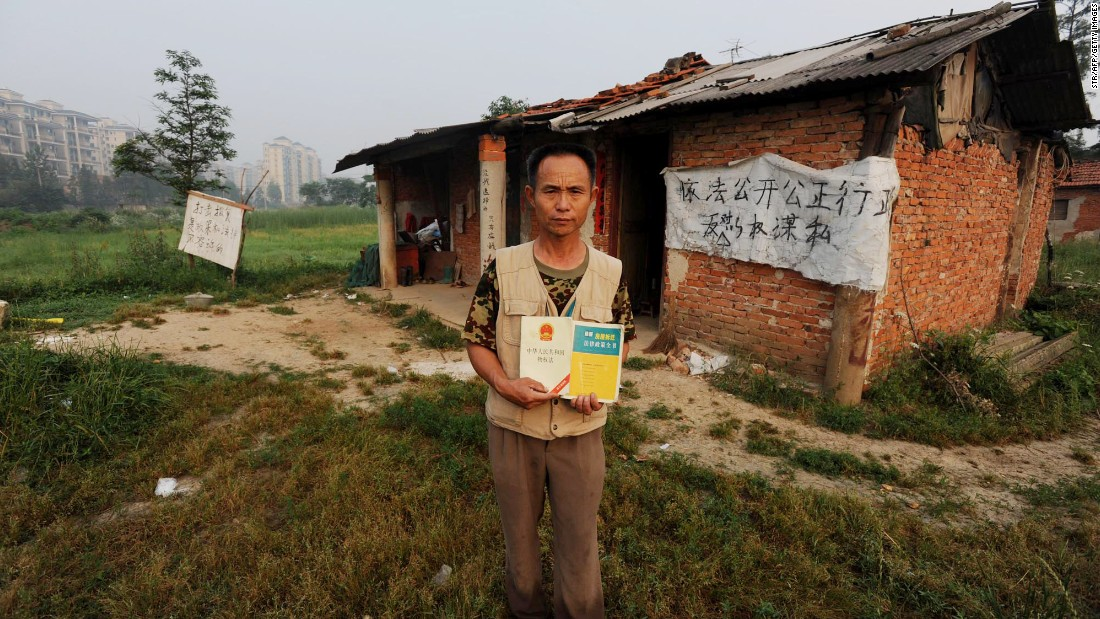 In a picture taken on June 6, 2010, Chinese farmer Yang Youde poses with a copy of China's Property Law on his farmland in front of his house on the outskirts of Wuhan, in central China's Hubei province. Yang uses improvised cannons, which are made out of a wheelbarrow, pipes and fire rockets, to defend his fields against property developers who want his land.