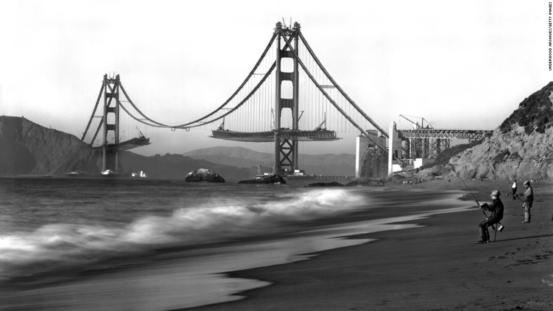 "Fishermen on Baker Beach enjoy the view of the Golden Gate Bridge under construction. Work on the bridge began on January 5, 1933, and lasted four years and four months. The span is painted a distinctive color named ""international orange."""