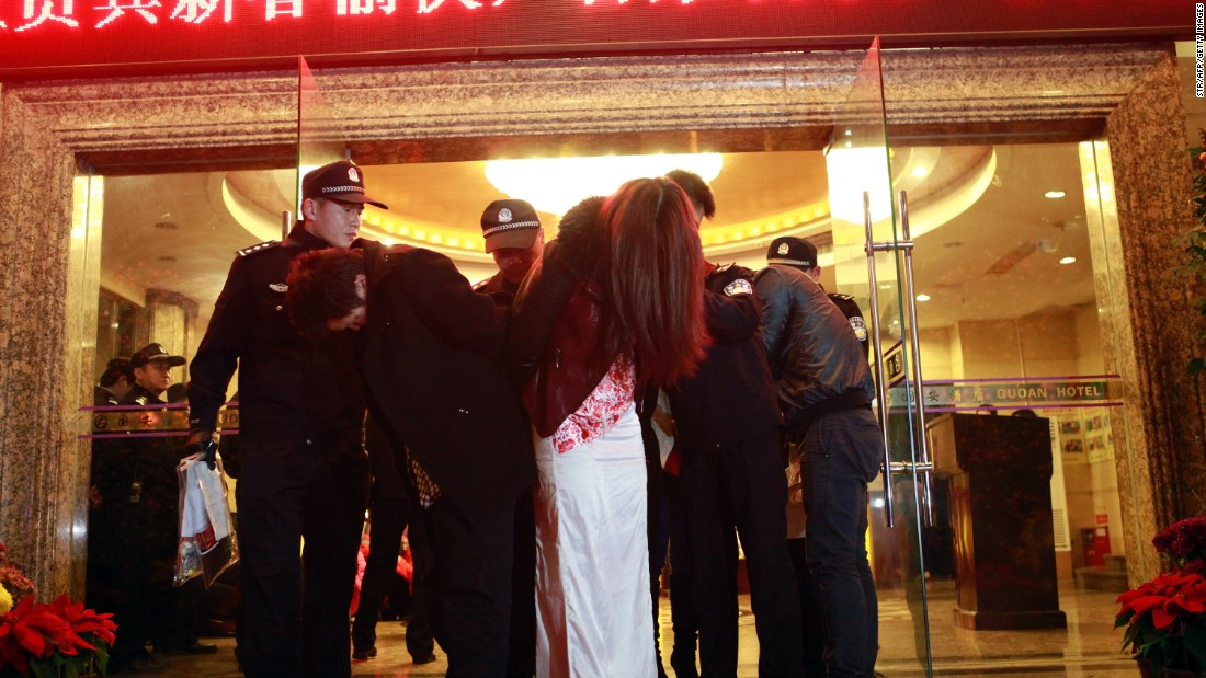 "This picture taken late on February 9, 2014 shows Chinese police taking away alleged sex workers and clients at an entertainment center in Dongguan, sometimes called China's ""Sin City."""