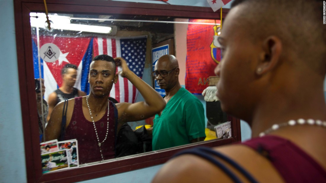 An American flag hangs next to a Cuban flag in an Havana barbershop in February.