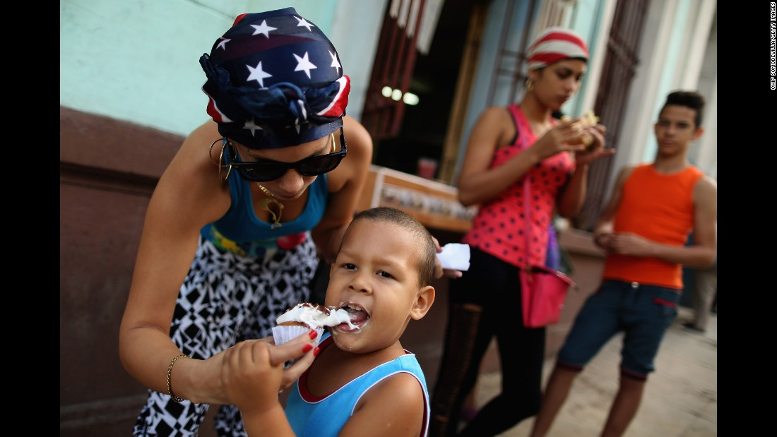 A woman wearing an American flag bandana gives her son some ice cream in Havana in January.
