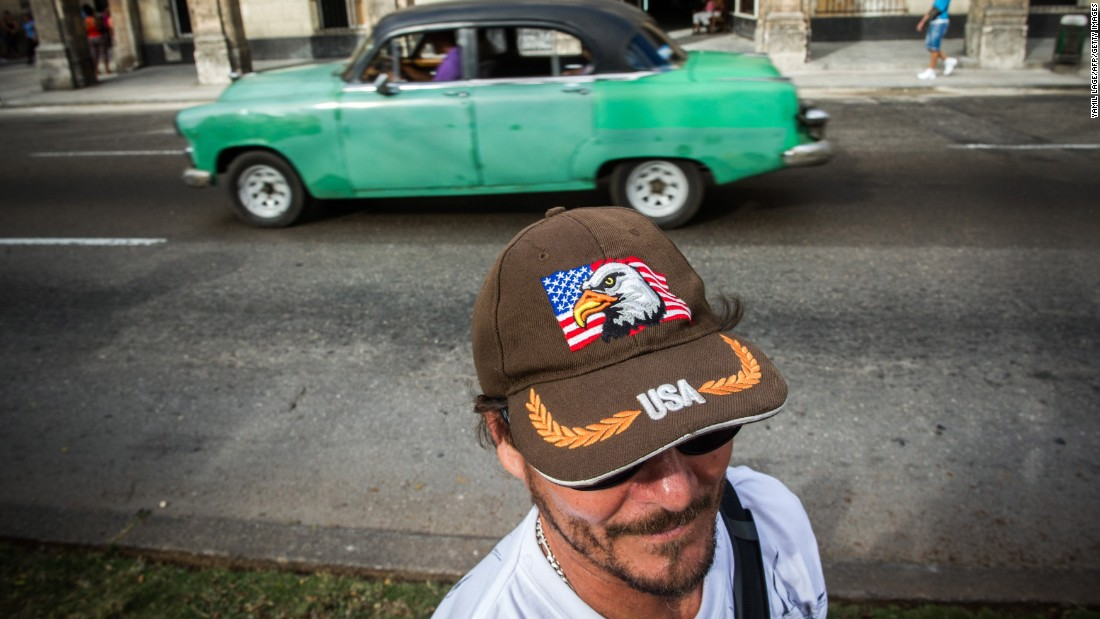 A car passes a man in Havana wearing a cap displaying the U.S. flag in February.