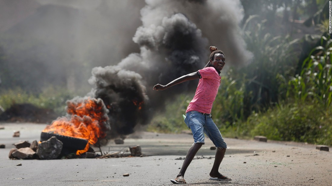 An anti-government protester throws a rock at police officers in Bujumbura on Thursday, May 21.