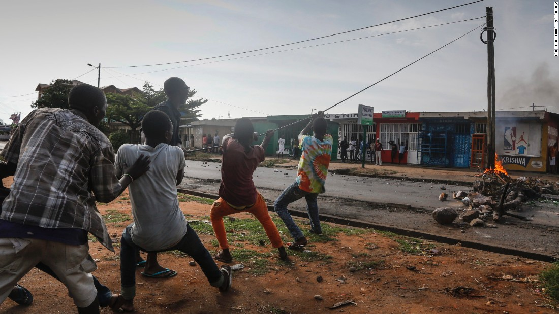 Protesters pull electrical cable to topple a power pole at an anti-government demonstration in Bujumbura on May 21.