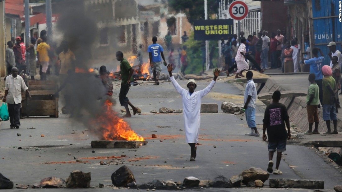 A protester stands by a burning barricade in Bujumbura on May 21.