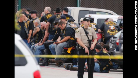 "A McLennan County deputy stands guard near a group of bikers in the parking lot of a Twin Peaks restaurant Sunday, May 17, 2015, in Waco, Texas. Waco Police Sgt. W. Patrick Swanton told KWTX-TV there were ""multiple victims"" after gunfire erupted between rival biker gangs at the restaurant."