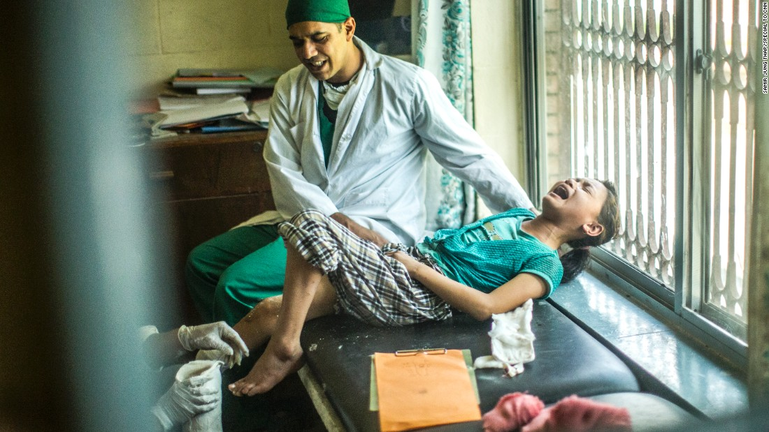 Dr. Bibek Banskota holds Maya Gurung as she screams in pain during a session to measure her leg. The photo was taken from a reflection in a mirror, so the image is reversed.