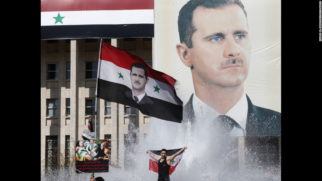 "Supporters of al-Assad celebrate during a referendum vote in Damascus on February 26, 2012. Opposition activists reported <a href=""http://www.cnn.com/2012/02/26/world/meast/syria-unrest/index.html"" target=""_blank"">at least 55 deaths</a> across the country as Syrians headed to the polls. Analysts and protesters widely described the constitutional referendum as a farce. ""Essentially, what (al-Assad's) done here is put a piece of paper that he controls to a vote that he controls so that he can try and maintain control,"" a U.S. State Department spokeswoman said."