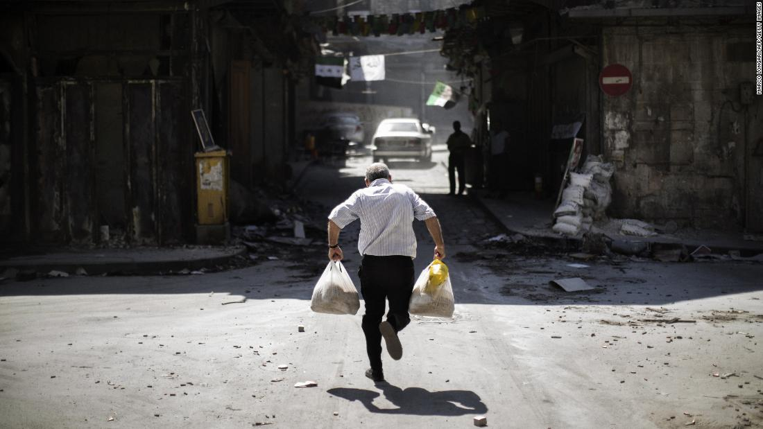 A Syrian man carrying grocery bags dodges sniper fire in Aleppo as he runs through an alley near a checkpoint manned by the Free Syrian Army on September 14, 2012.
