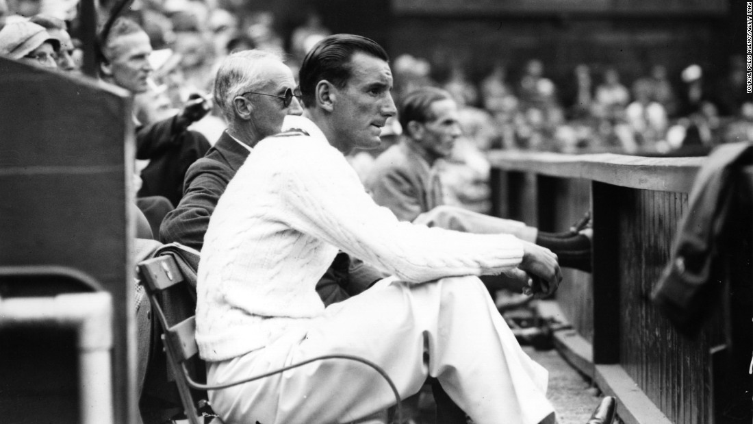 The 1936 champion Fred Perry takes a seat on a courtside bench to enjoy the match between Donald Budge and Bunny Austin.