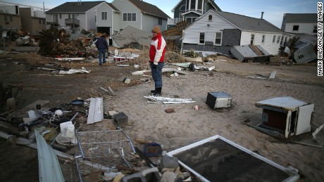 David Mccue (C), looks for pieces of his beach house that was completely demolished by Superstorm Sandy on November 25, 2012 in Seaside Heights, New Jersey.