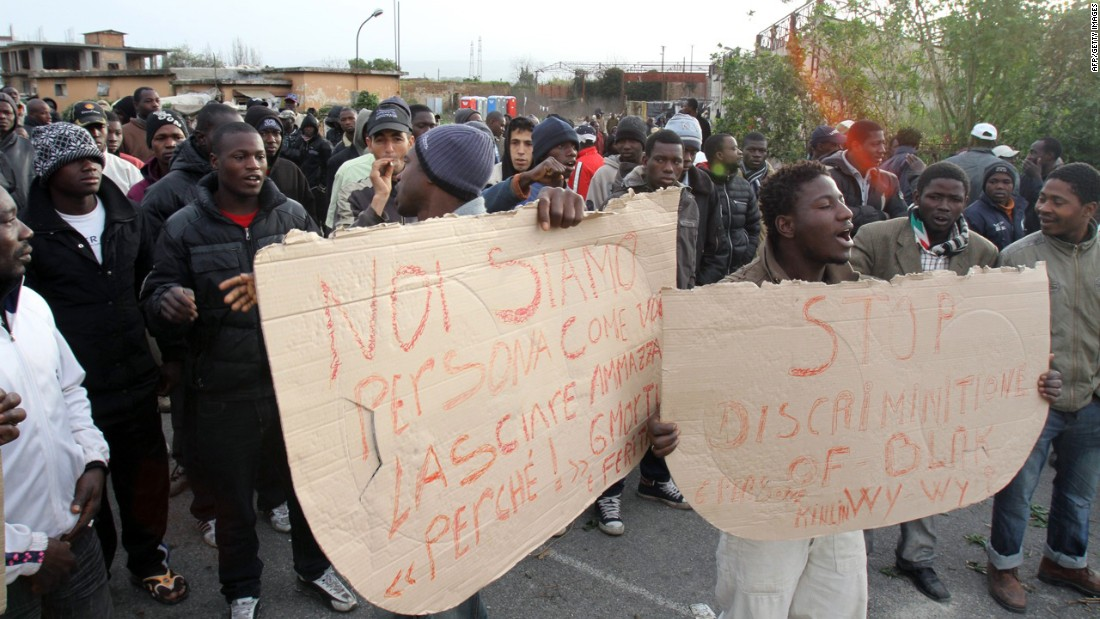 Rosarno has seen conflict between African migrants and the native population in recent years. Here, immigrant workers hold placards as they protest in the Calabrian town in 2010.