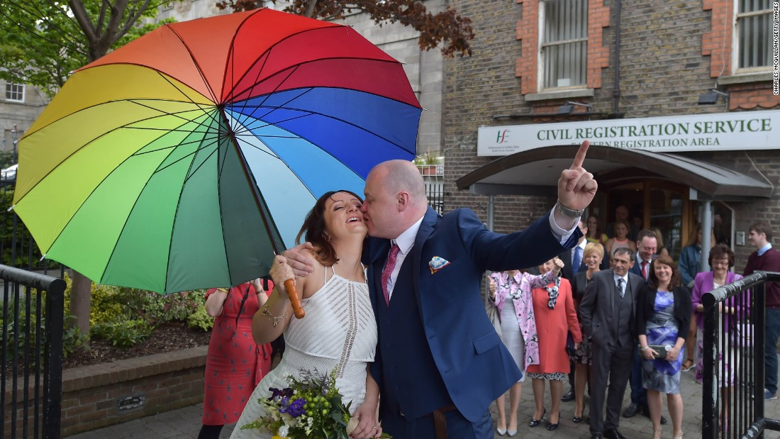 "Newly married couple Anne and Vincent Fox kiss in Dublin on Friday, May 22, under a rainbow umbrella, showing their support for the ""yes"" side in the same-sex marriage referendum.<br />"