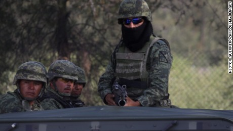 Mexican soldiers stand guard at the ranch where gunmen took cover during an intense gun battle with the police, along the Jalisco-Michoacan highway in Vista Hermosa, Michoacan State, on May 22, 2015. At least 37 people were killed in the gunfight in Mexico's troubled western state of Michoacan, in one of the bloodiest clashes in the country's drug war. Two police officers also died in the shootout in the municipality of Tanhuato, near the border with Jalisco state, a federal government official told AFP.