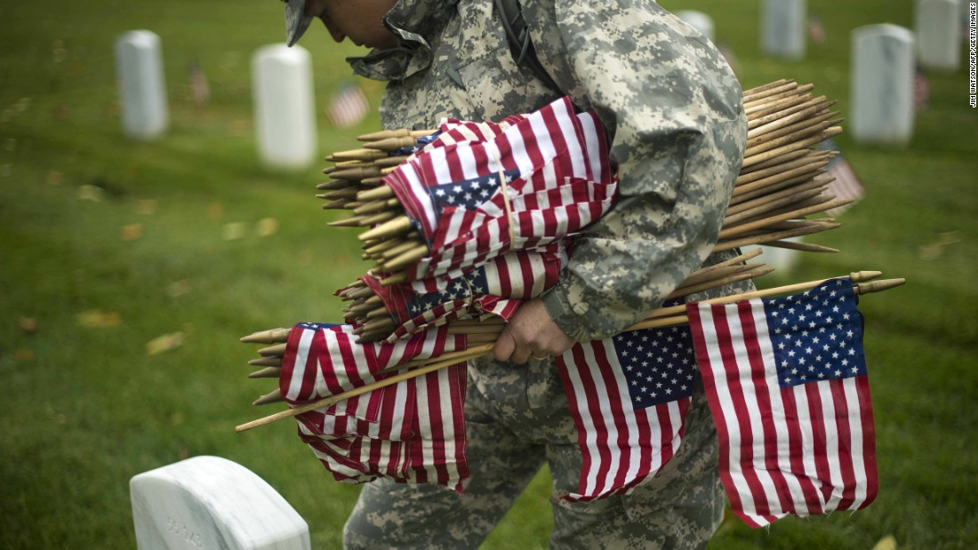 A soldier places flags in Arlington National Cemetery on May 21.