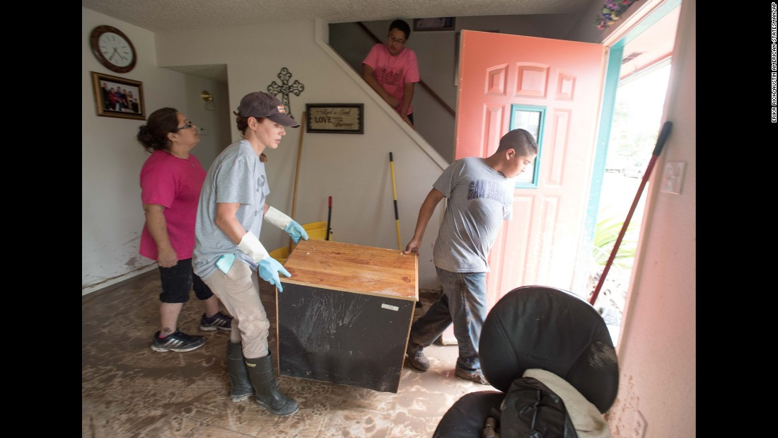Heather Williams and Jayden Martinez Corpus assist the Villegas family in clearing flood-damaged furniture from their home in San Marcos on May 24.