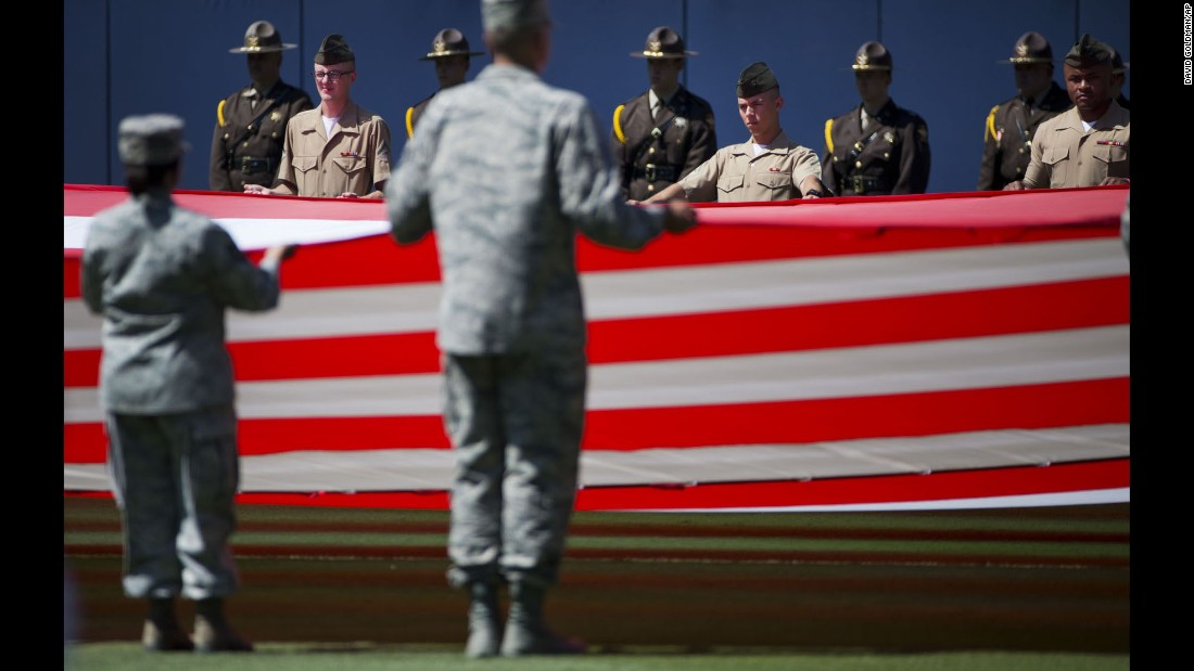 Members of the military stand at attention while unveiling a giant American flag before the start of a Major League Baseball game in Atlanta on Saturday, May 23.