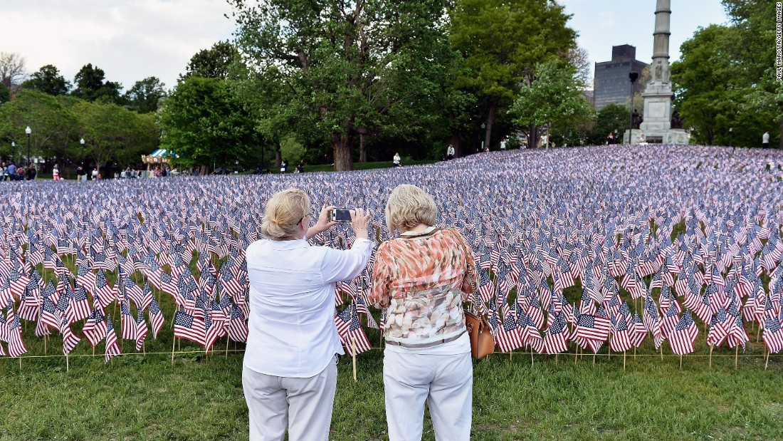 Visitors in Boston take a picture May 22 of American flags placed by the Massachusetts Military Heroes Fund. The flags represent fallen military members from Massachusetts.