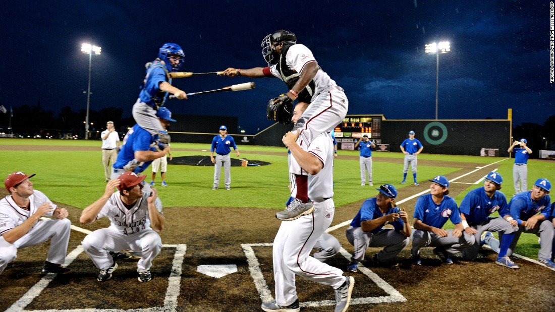 Baseball players from Troy and Texas-Arlington joust playfully during a weather delay in the Sun Belt tournament on Wednesday, May 20.