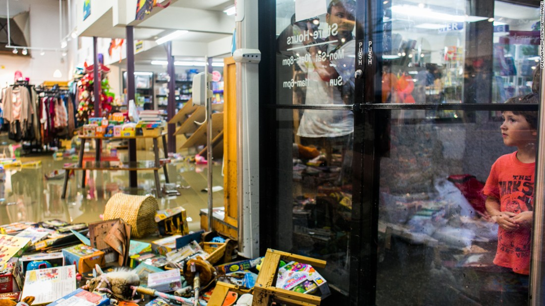 Lucas Rivas looks into a flooded store in Austin, Texas, on May 25.