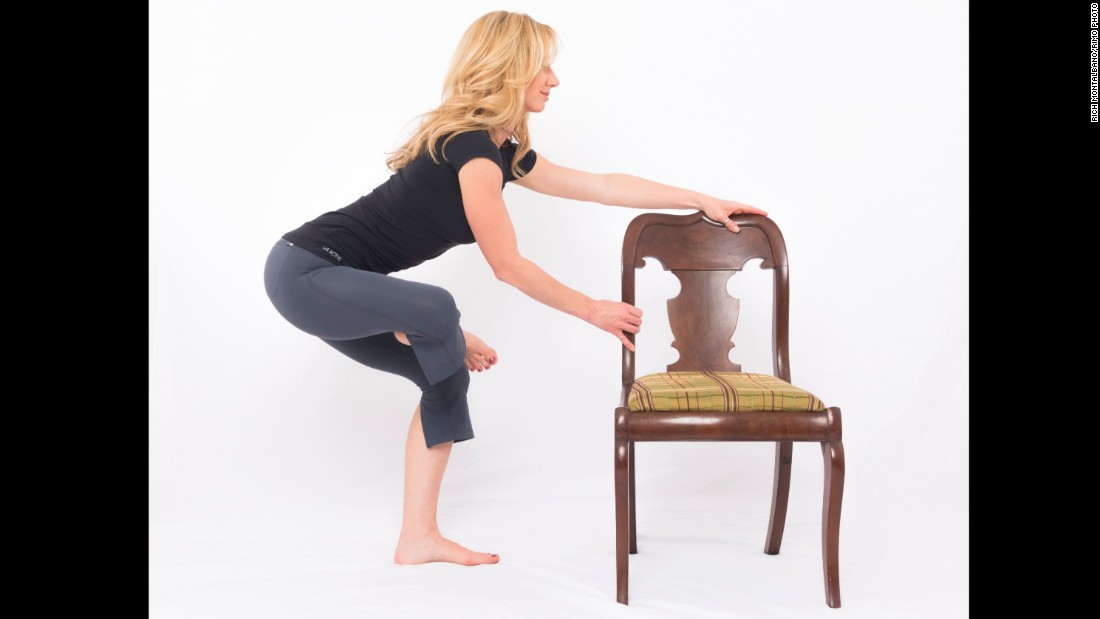 Bracing yourself by holding your chair or desk, shift your weight to your left leg. Place your right foot on your left thigh above your knee in a figure-four position. Exhale as you sit back as deeply as you can without discomfort. Hold for five long, deep breaths. Repeat on the other side.