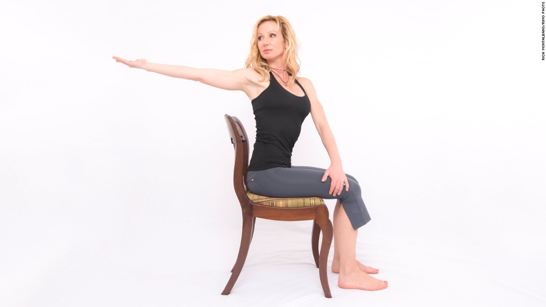 From a seated position at your desk, inhale as you reach your right arm forward at shoulder height with your palm up. Exhale as you reach back to the right, internally rotating your left lower ribcage to facilitate the twist. Activate the muscles just below your right shoulder blade to pull it down toward your waist and slightly in toward your spine. Hold for three long, deep breaths. Repeat on the other side. If your chair back is higher than shoulder level, you'll need to angle your lower body so that your knees point in the opposite direction you're twisting to give you enough room to reach behind you.