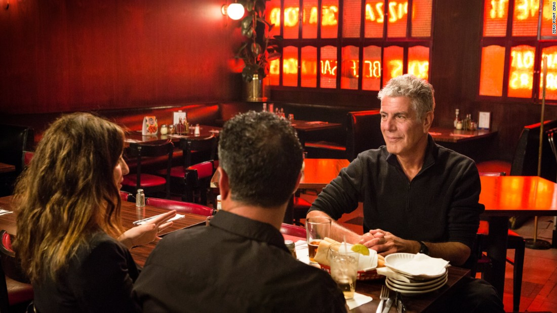Bourdain listens over dinner as the husband-wife comedians discuss how people often think of New Jersey as an industrial wasteland because of the refineries along the turnpike.