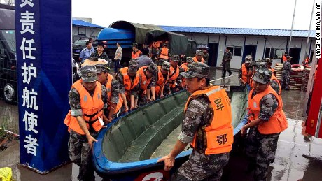 "Chinese soldiers carry a boat to search for survivors after a ship carrying at least 458 people sank during a storm on the Yangtze River in Shishou city, central China's Hubei province, 2 June 2015. A passenger ship carrying at least 458 people sank Monday (1 June 2015) night during a storm on China's Yangtze River and most remained unaccounted for as of early Tuesday, the official news agency Xinhua reported. The ship, identified as the Eastern Star, had been en route from Nanjing, the capital of Jiangsu Province in eastern China, to Chongqing in southwest China, one of the country's largest cities. Xinhua said the vessel carried 405 Chinese passengers, five travel agency workers and 47 crew members. ""Eight people have been rescued,"" the agency said. ""Rescue work is hampered by strong wind and heavy rain."" The agency added that the captain and chief engineer, who were among the rescued, asserted that the ship had been caught by a cyclone as it navigated a section of the river that traverses Hubei Province and that ""the ship sank quickly.""(Imaginechina via AP Images)"