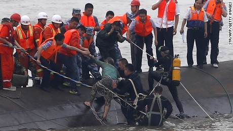 A survivor (C-green top) is rescued by divers from the Dongfangzhixing or 'Eastern Star' vessel which sank in the Yangtze river in Jianli, central China's Hubei province on June 2, 2015.