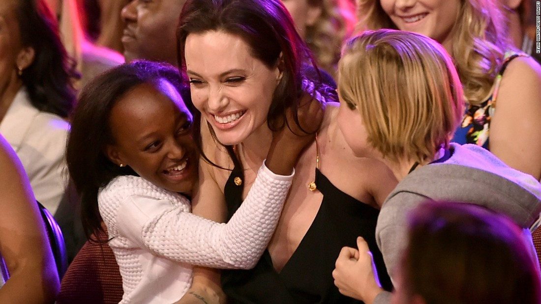"""Jolie hugs her children Zahara, left, and Shiloh after winning an award during Nickelodeon's Kids' Choice Awards in March 2015. Jolie won Favorite Villain for her role in """"Maleficent."""""""