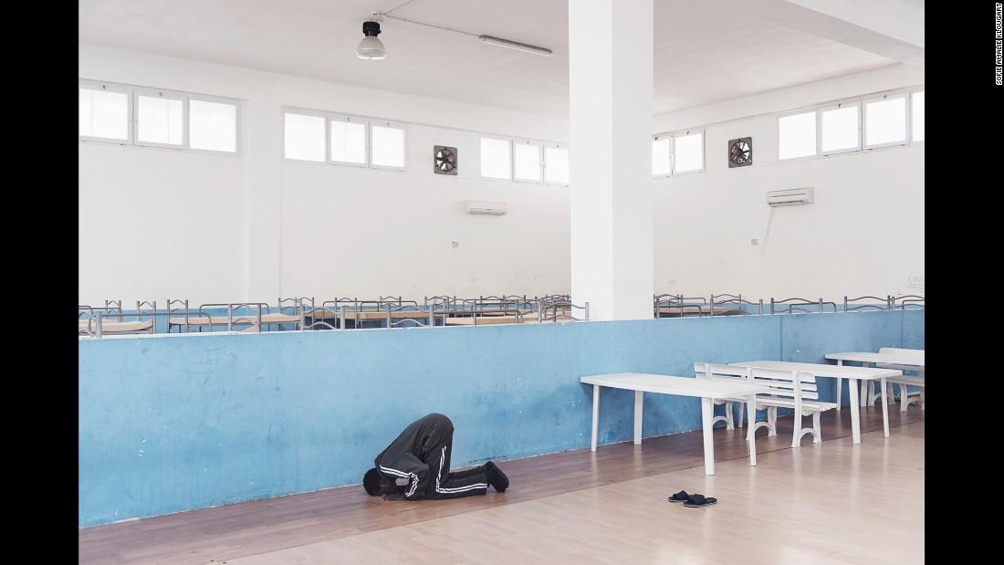 Amdi prays in a nearly empty room.