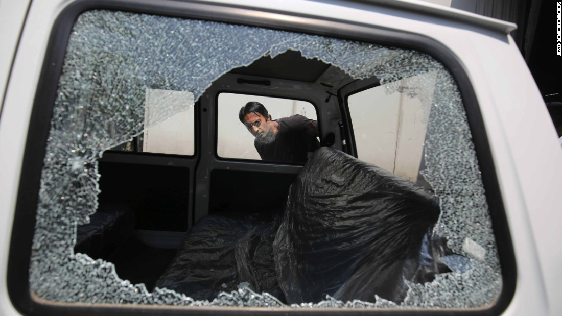 A man in Srinagar, India, looks inside a vehicle that was damaged in a grenade attack on Monday, June 1. One person was injured in the attack, which targeted a cell phone tower, police said.