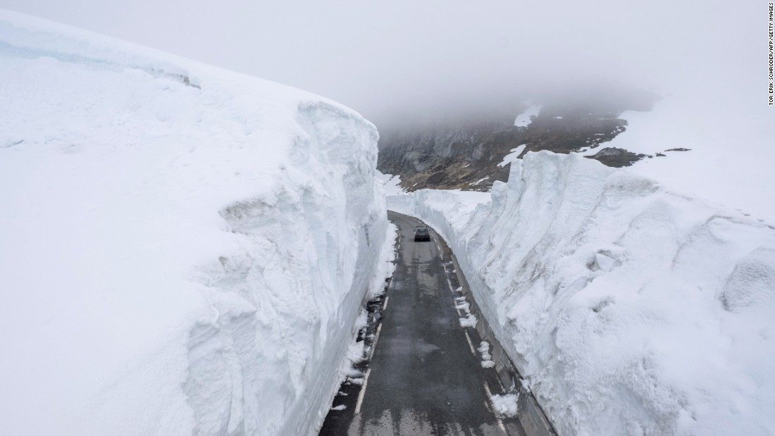 A car drives past walls of snow on a mountain road in Norway on Saturday, May 30.
