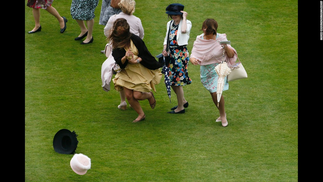 Women run after their hats Tuesday, June 2, during a windy garden party at Buckingham Palace in London.