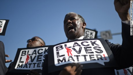 Men holding signs reading 'Black Lives Matter' march in the 30th annual Kingdom Day Parade in honor of Dr. Martin Luther King Jr., January 19, 2015 in Los Angeles, California. 2015 is the 50th anniversary of the historic 1965 Selma to Montgomery Alabama freedom marches which played a pivotal role in the civil rights struggle for racial equality in the U.S. AFP PHOTO / ROBYN BECK