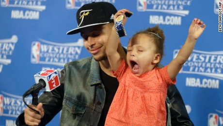 Golden State Warriors guard Stephen Curry is joined by his daughter Riley at a news conference after Game 5 of the NBA basketball Western Conference finals against the Houston Rockets in Oakland, Calif., Wednesday, May 27, 2015.