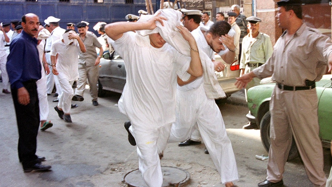 About 50 men accused of breaking laws covering obscenity and public morality cover their faces as they enter a state security court for their trial in Cairo, Egypt in July, 2001.