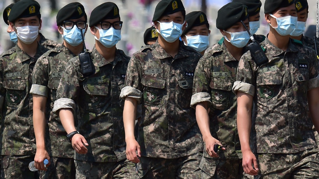 South Korean soldiers wear face masks as they march after a ceremony marking the 60th anniversary of Korean Memorial Day at the National Cemetery in Seoul on June 6, 2015.