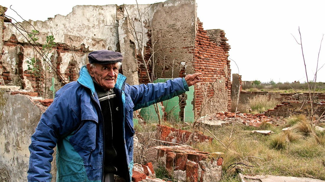After being buried under 33 feet of floodwater for about 25 years, Epecuen re-emerged in 2009. Novak points at the ruins of his primary school.