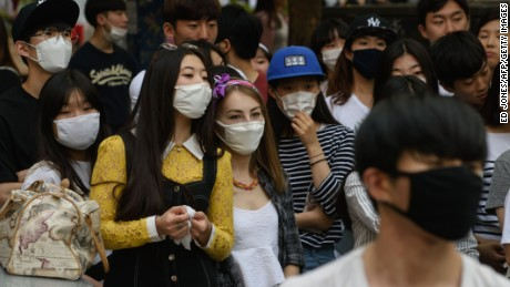 People wearing face masks watch a K-Pop performance on a street in the popular student area of Hongdae in Seoul on June 7, 2015. South Korea reported its fifth death from MERS as the government on June 7 vowed 'all-out' measures to curb the outbreak that was threatening to spread nationwide, including tracking mobile phones of those in quarantine. AFP PHOTO / Ed Jones (Photo credit should read ED JONES/AFP/Getty Images)